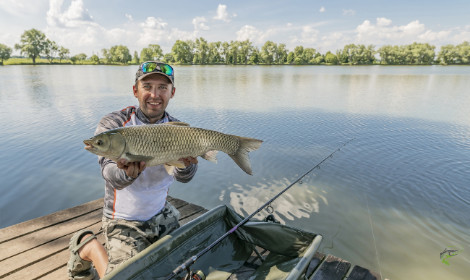 How to Catch Grass Carp - Man holding grass carp with lake in background