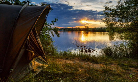 Carp Fishing Tips - Camping gear and carp rods beside a lake with sunset
