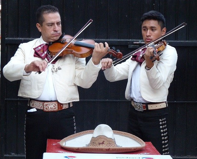 Two mariachis dressed in black and white playing violins. A white sombrero at the front.