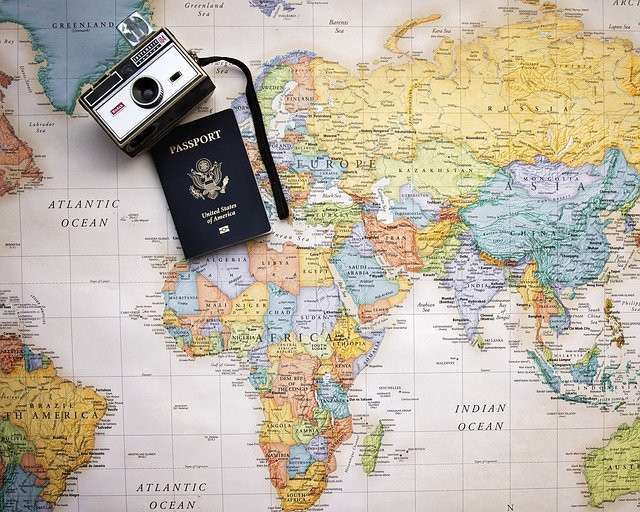 World map with an American passport and a camera over it.