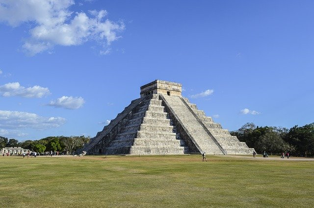Centered pyramid of Kukulcan and some people in the distance to the left.