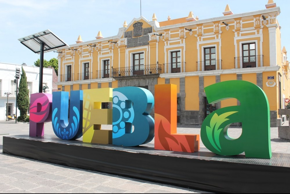 Yellow building with colorful letters in the fron in purple, blue, yellow, orange and green.