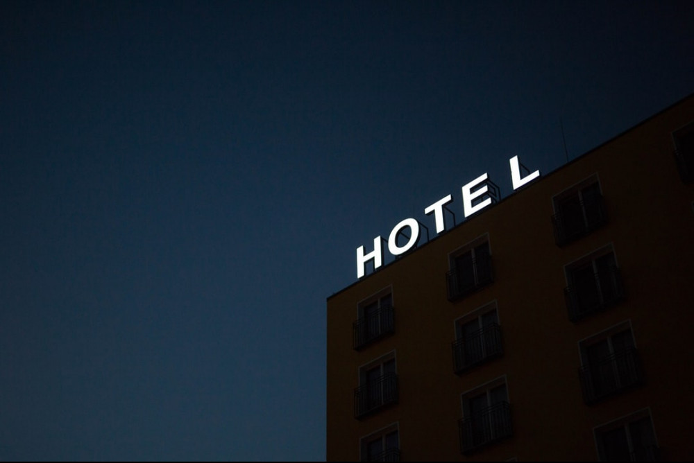 Corner of a black building with the word hotel in white against a dark blue sky.