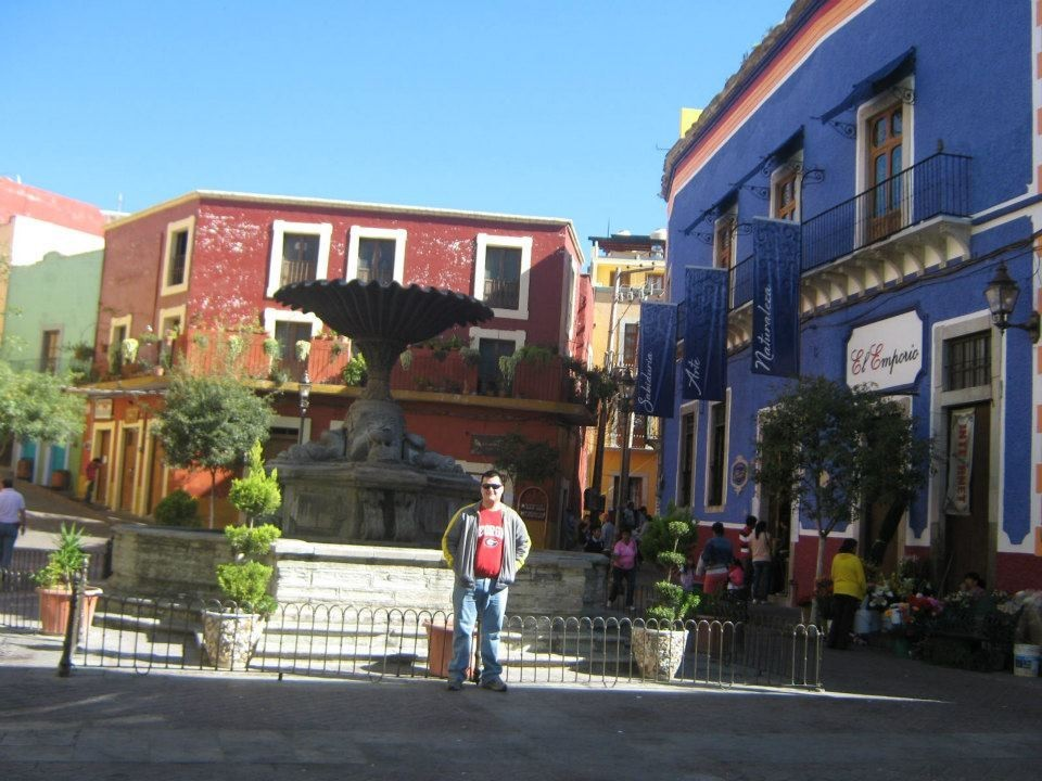 One of Guanajuato many plazas with a fountain in the center and red and blue buildings in the back and to the right.