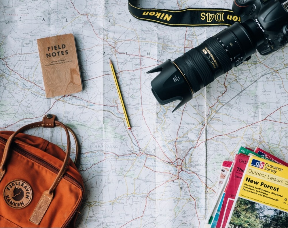 Map, pencil, notebook, camera, tourism brochures and a bag.