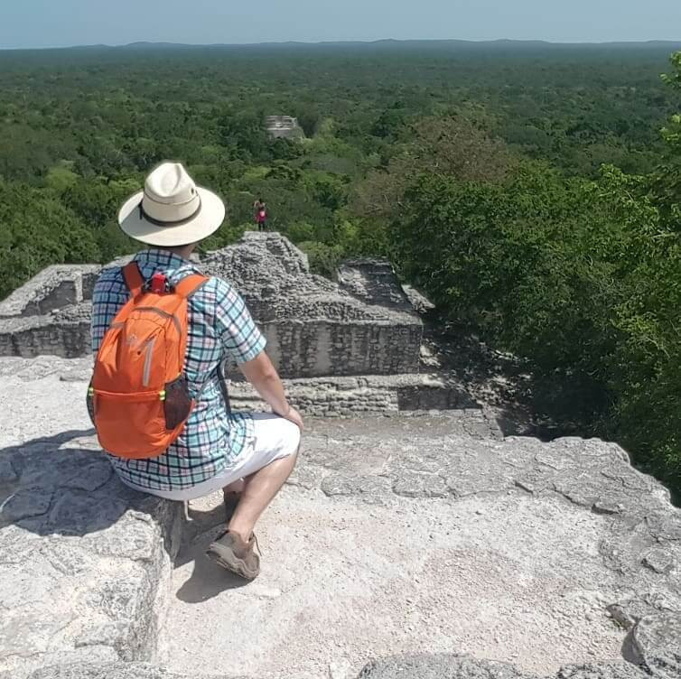 Young man sitting on top of a pyramid and looking over the tropical rain forest in Calakmul.