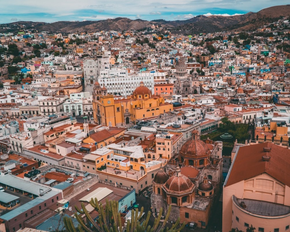 Aerial view of Guanajuato City with its yellow basilica in the center and several colorful buildings surrounding it.