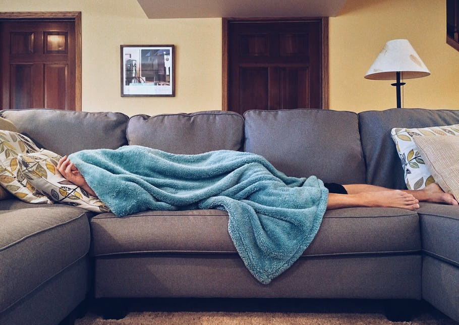 Woman lying on a couch, covered by a blue blanket.