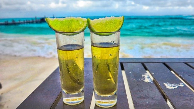 Two glasses of tequila with lime on top.
