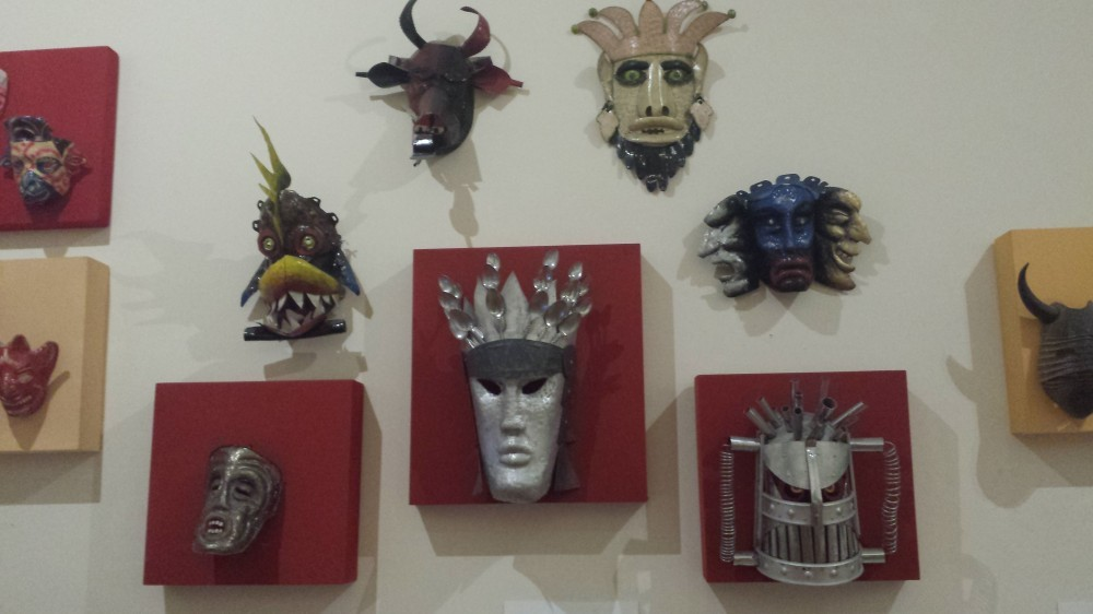 Several masks of various kinds hanging on a white wall.