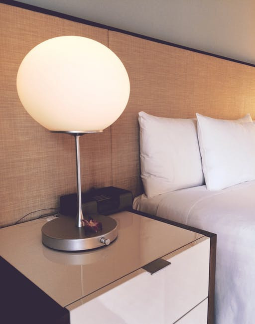 Bed with a nightstand and a circular lamp to the left.