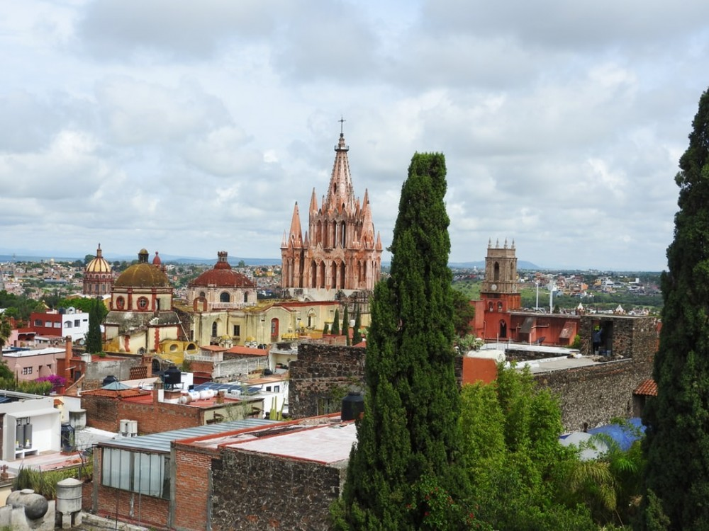 City landscape with several colonial buildings in the back with an outstanding pink, neo-Gothic style cathedral.