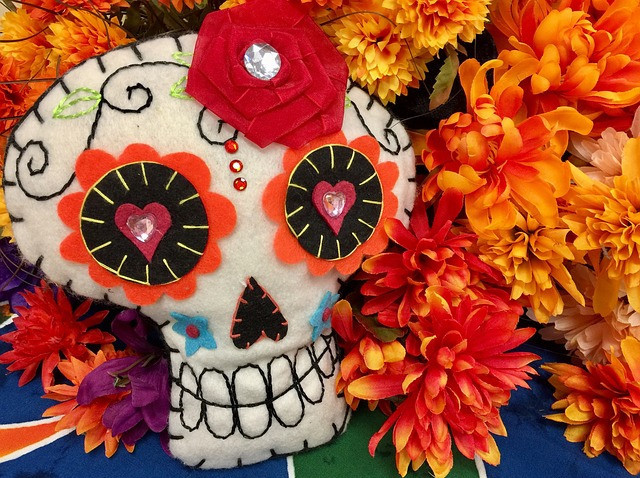 White skull surrounded by marigolds depicting Dia de Muertos.
