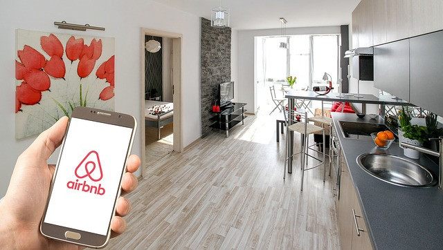 Hand holding a cell phone with the AirBnB logo and an apartment dining room and living room in the background