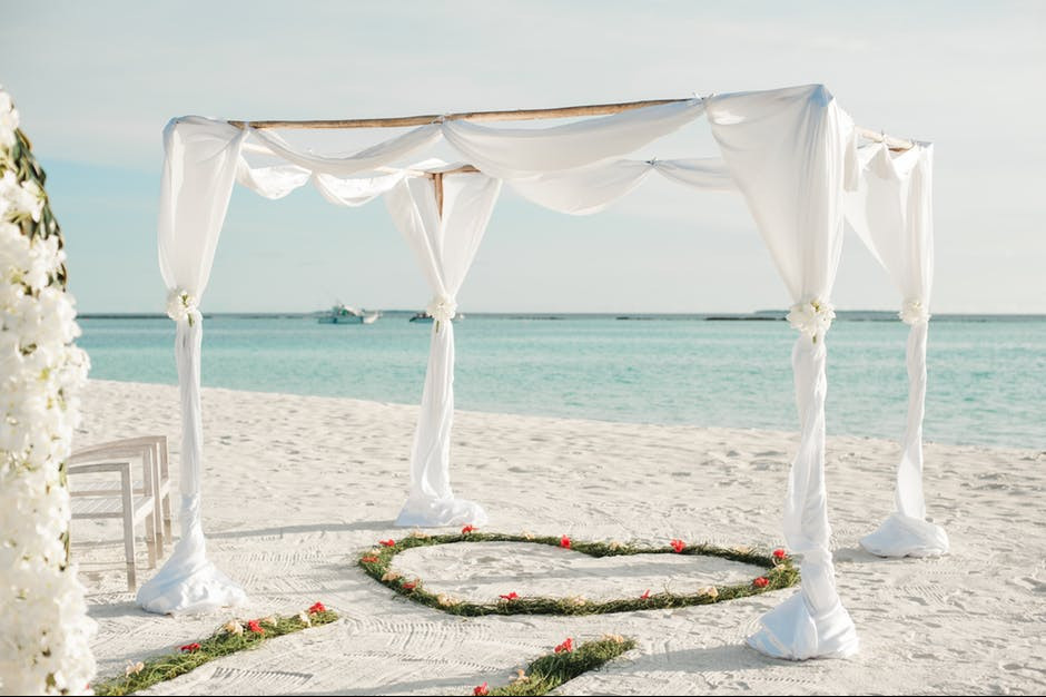 White canopy on the edge of the beach with heart of roses underneath.