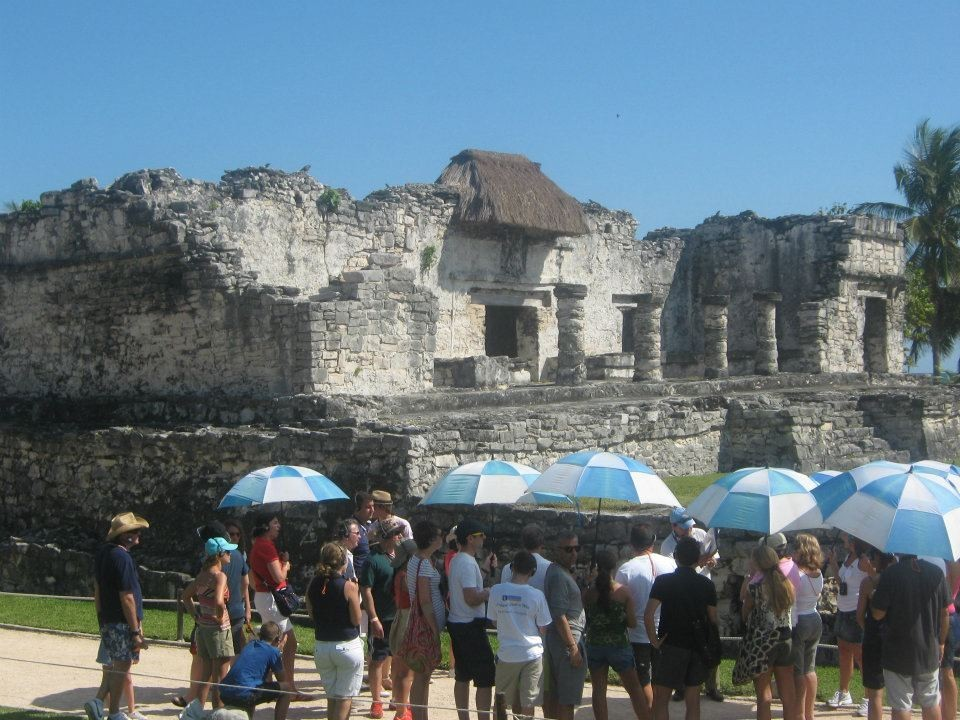 Several tourists taking a tour of some Mayan ruins.