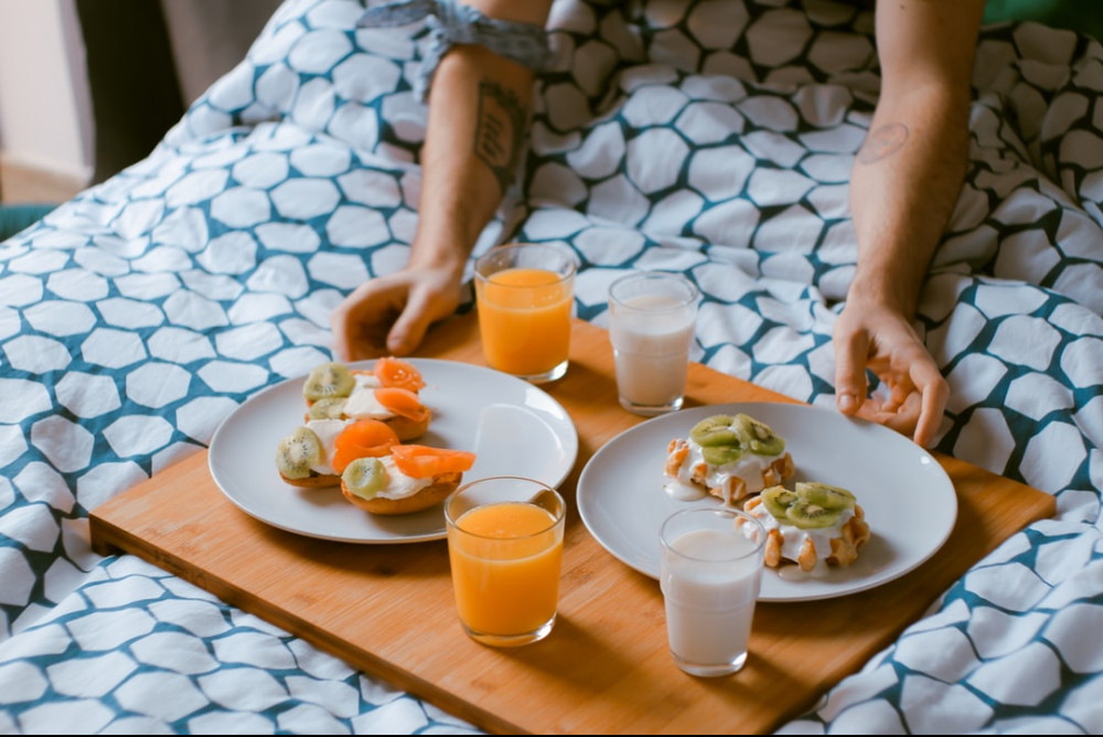 Two hands holding a food tray with two plates with fruit and four glasses with orange juice and milk.