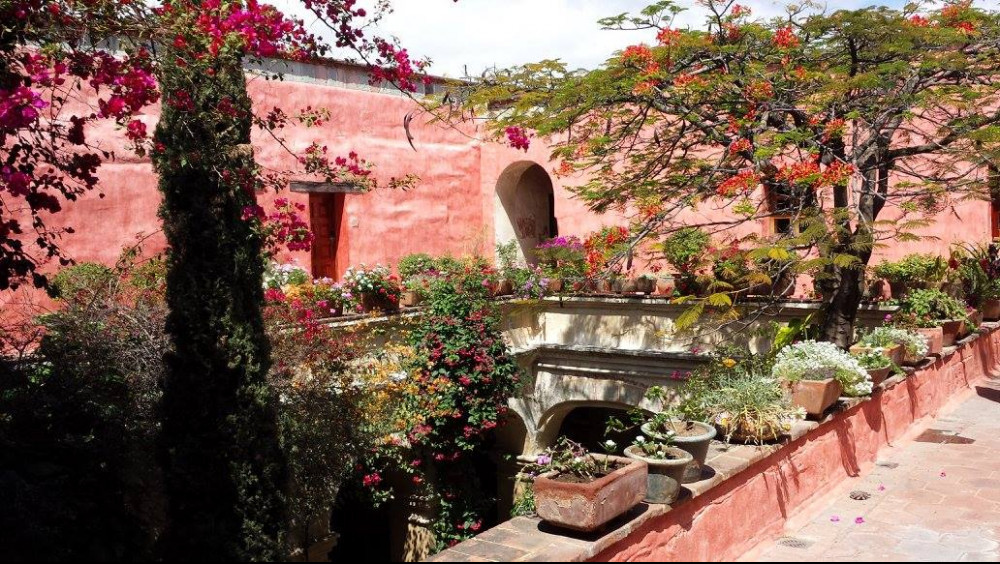 Second floor of ancient red building with a terrace and lots of flowers and other plants overlooking two trees.