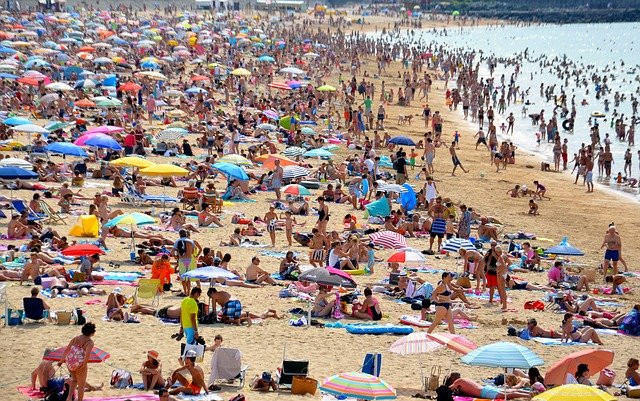 Crowded beach with lots of tourists and colorful umbrellas.