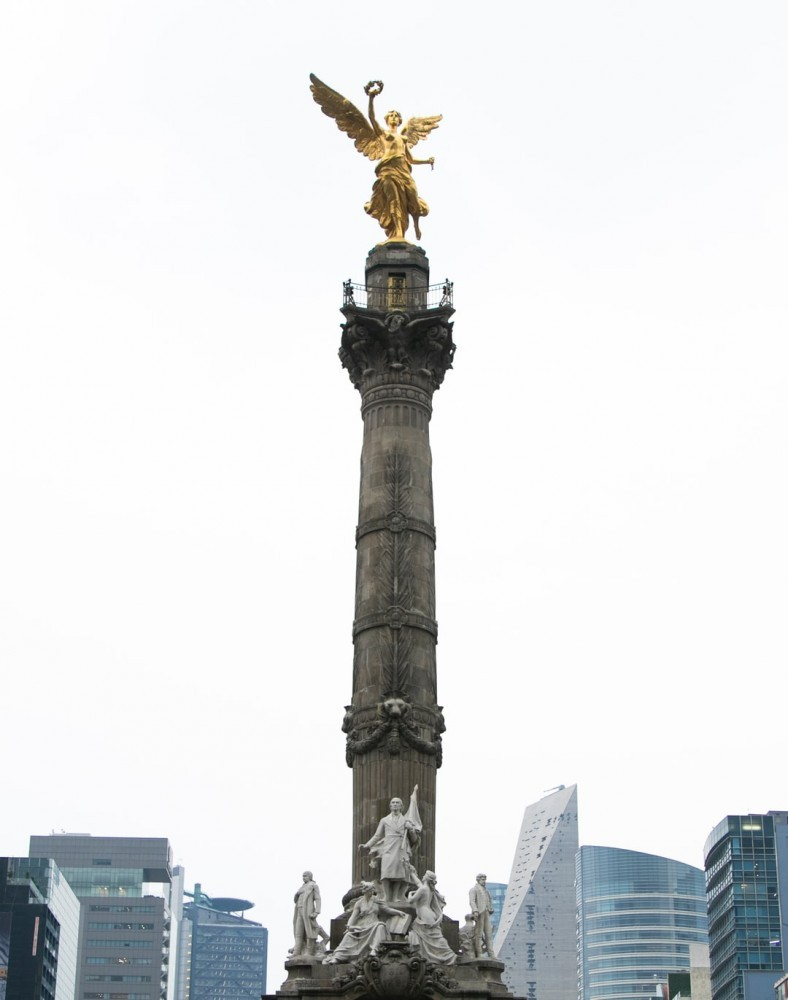 Golden winged angel on a pedestal with several marble figures below it and a few buildings in the background.