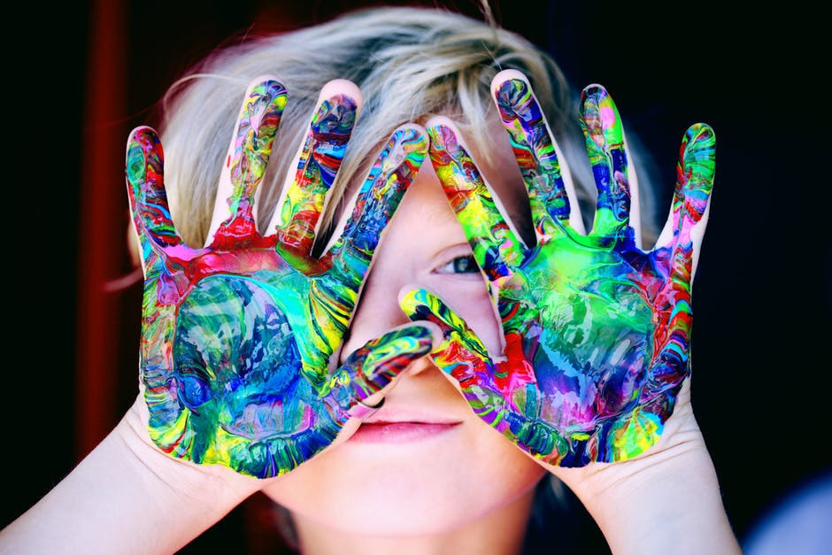 Little kid showing both of his palms painted in different colors.