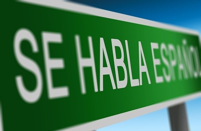 Green sign with white letters that read Se habla espanol.