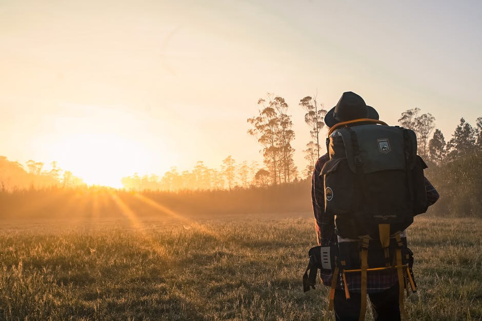 Traveler carrying a large backpack and facing the horizon.