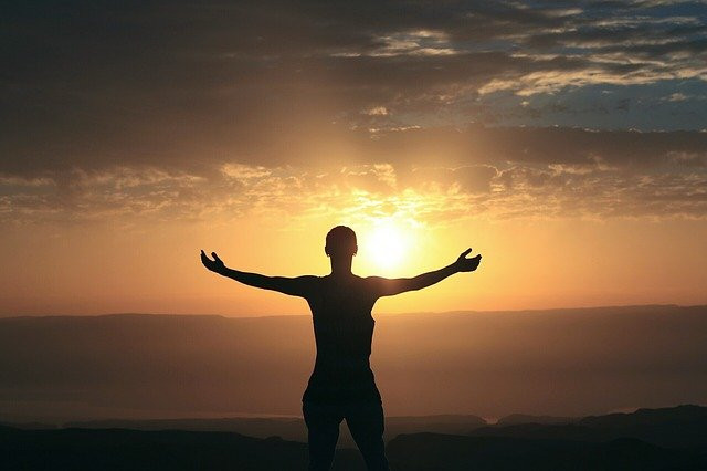 Woman silhouette facing the sun and holding out both of her hands.