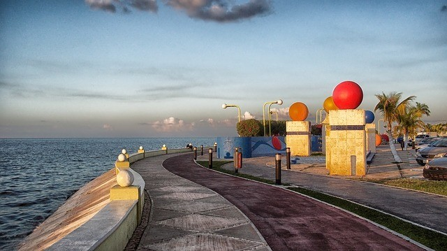 Seawall with a running track and colorful round sculptures to the right and the sea to the left.