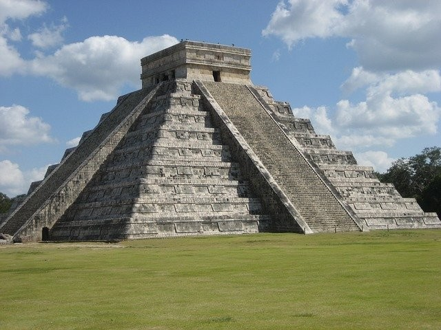 Mayan pyramid with the sky behind it full of clouds.