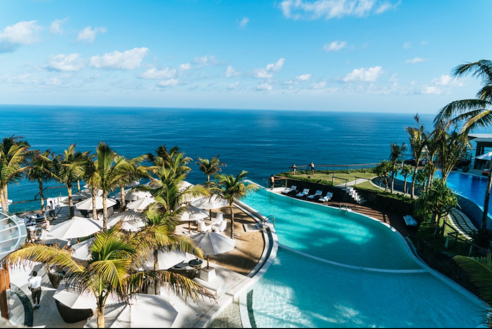 Resort overlooking the sea with a swimming pool in the middle and several palm trees lining it up.