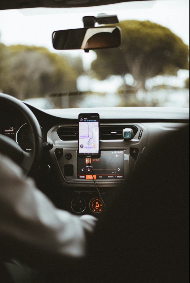 Inside of a car with a cellphone in the center featuring the Uber app.