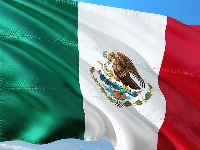 Mexican flag in green, white and red with an eagle devouring a snake in the center.