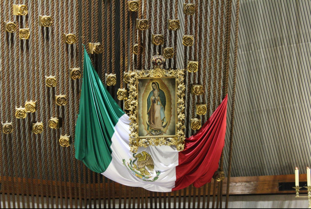 Picture of the Virgin of Guadalupe holding the Mexican flag underneath.