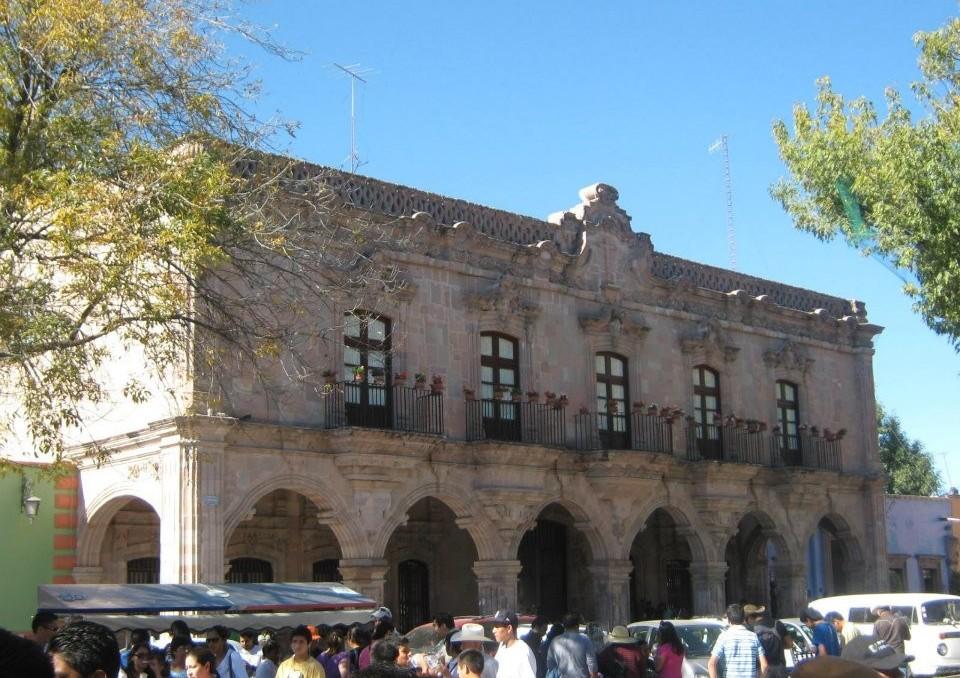 Facade of a gray building hosting the Casa de las visitas.