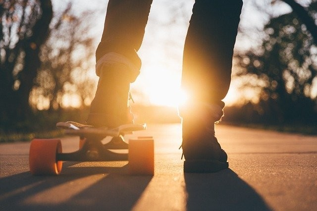 Picture of a person't legs with a skateboard facing the sun.