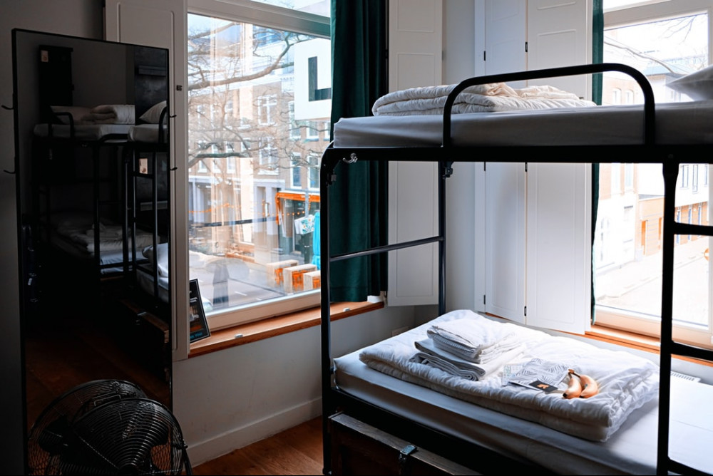 Bunk bed with folded sheets on top and an open window overlooking the street.
