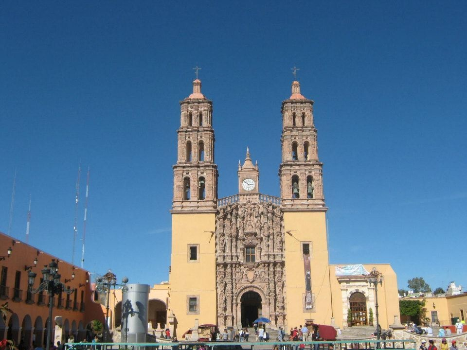 Tan church with two towers and a large clock in the middle.