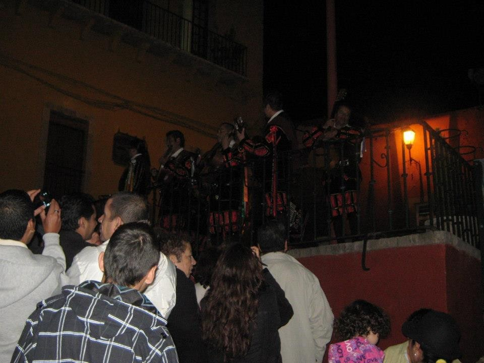 Group of people seen from behind and a musical band in front of them.