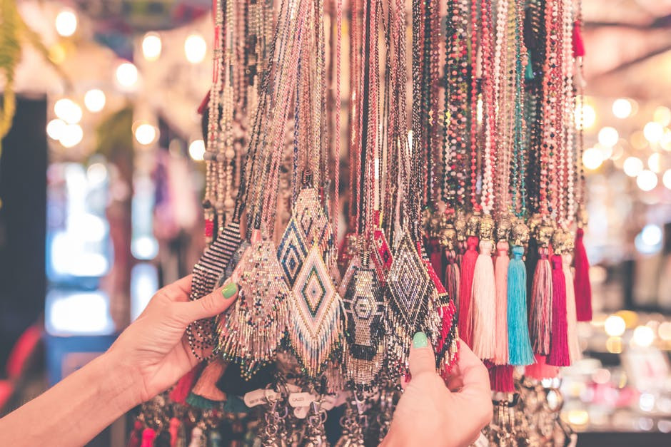Hand holding a couple of colorful necklaces.