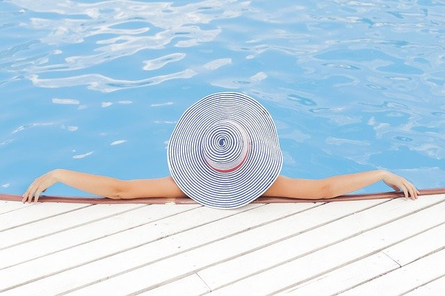 Woman inside a pool wearing a hat seen from the back.
