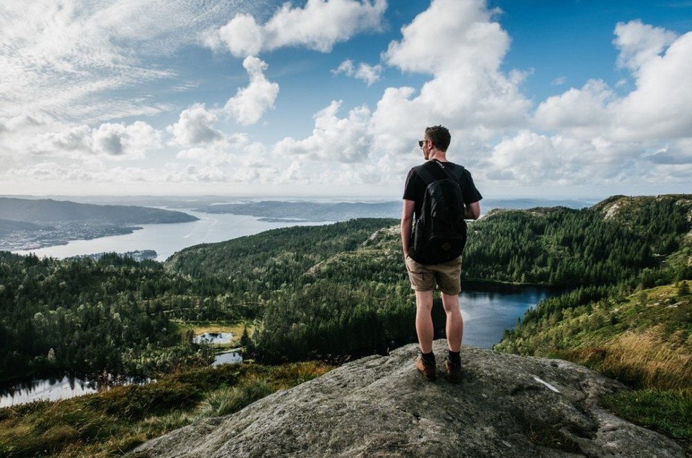 walking and hiking safety tips, image shows a man standing on top of a rock