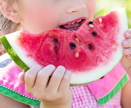 Child eating watermelon, an example of using nutritious foods to maintain healthy blood sugar levels, very important in being able to self-regulate!