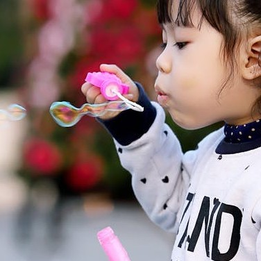 Little girl blowing bubbles, one of the fun activities that develop focus and assist self-regulation.