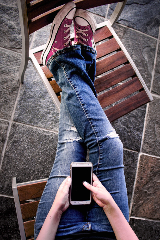 How to Beat Stay-At-Home Mom Boredom - Woman on Cellphone Propping Feet on Chair