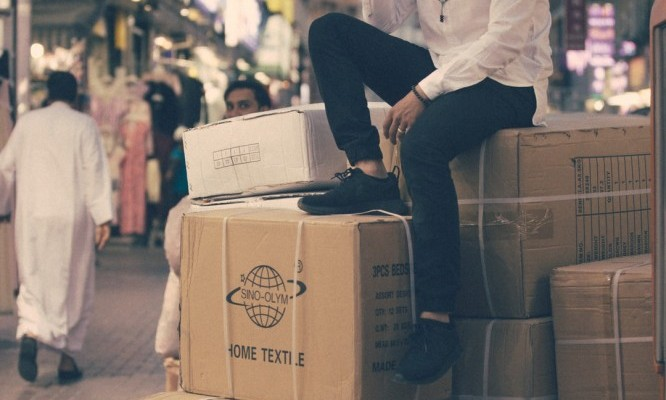 person sitting on drop shipping boxes