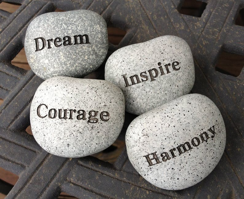 rocks imprinted with the words harmony, inspire, courage and dream