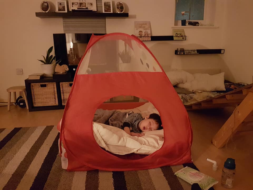 a young boy sleeping in a play tent