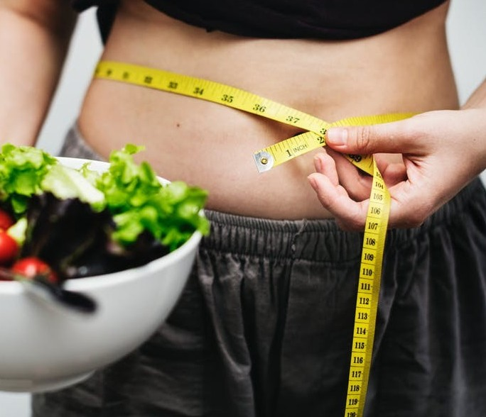 Women eating healthy with tape measure recording her weight loss