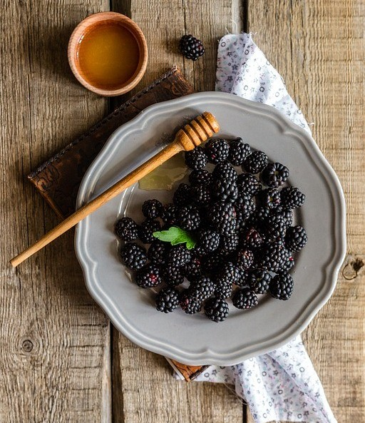 Blackberries in dish with honey